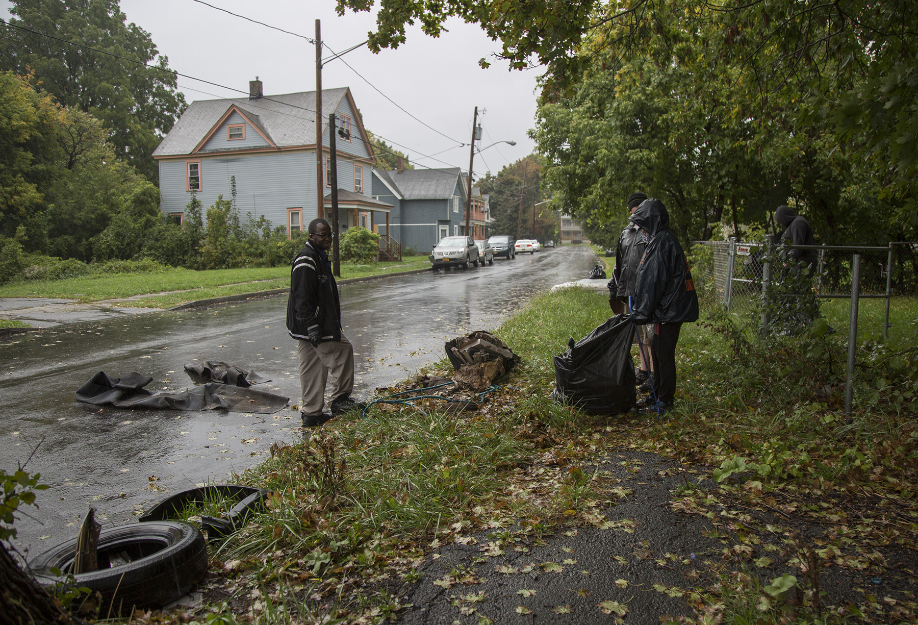 Arlene Brodbek, Pete Nicolini and Jerome Sanders work to clean up an area that has become a dumping site for tires, old TVs, rugs and more during the South Side cleanup organized by Believe in Syracuse on Oct. 8. | Aubrey Moore, Staff Photo