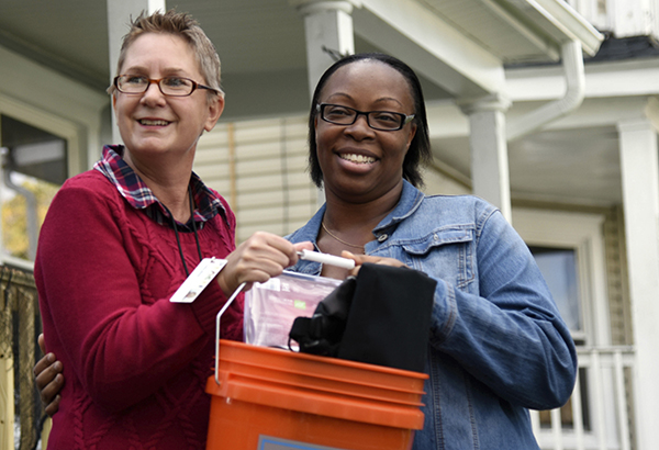 PEACE Inc. representative Sally Ward, left, presents homeowner Tanesha Keene with a bucket of home safety items donated by The Home Depot, including smoke detectors for her children's rooms.
